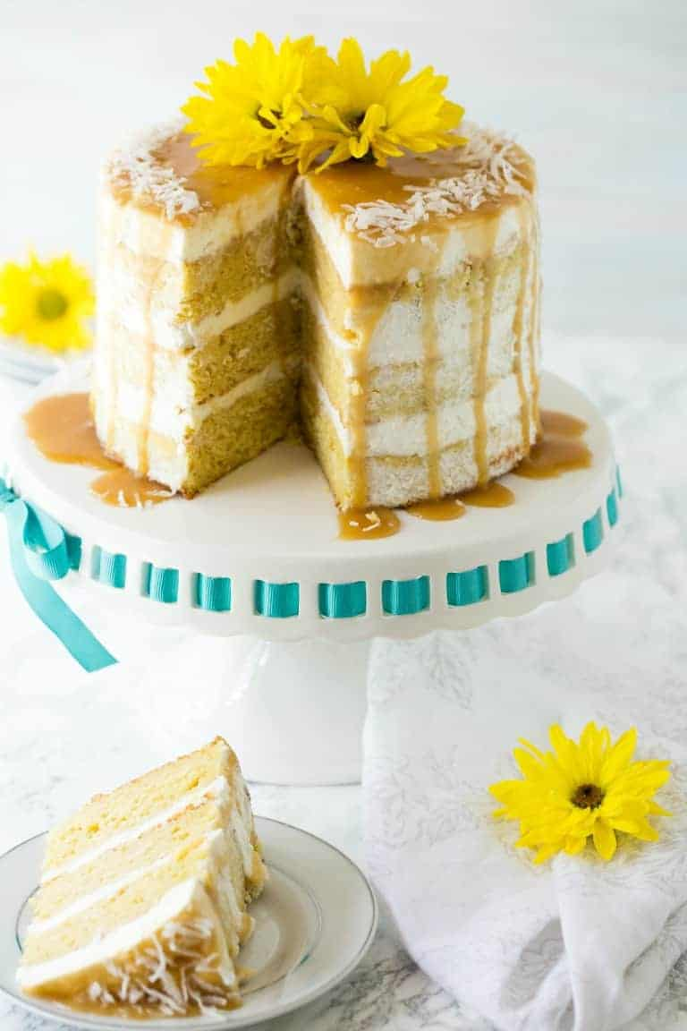 mango cake on a cake stand with slice removed