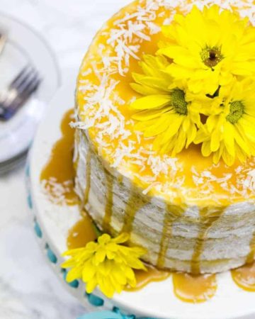 overhead view of mango cake on a cake pan with yellow flowers on top
