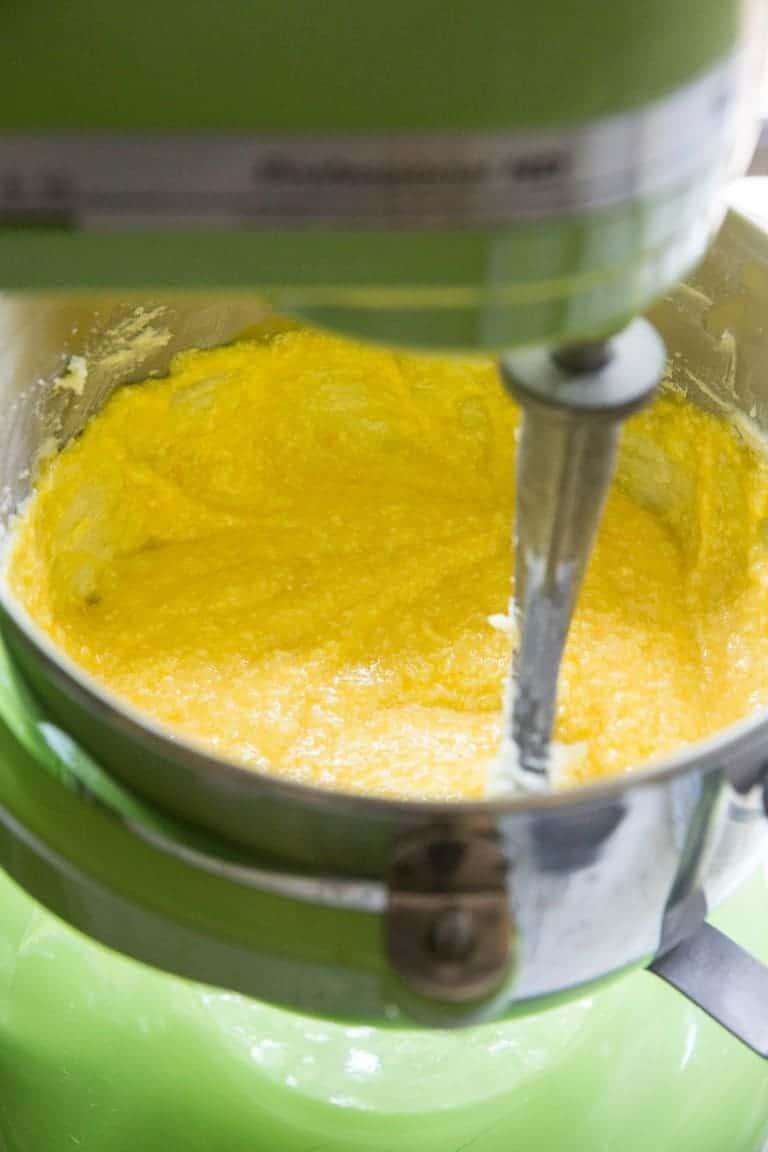 mango cake batter inside a green stand mixer