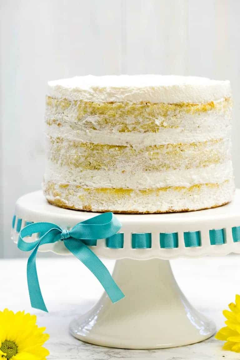 mango cake on white cake stand with blue ribbon threaded