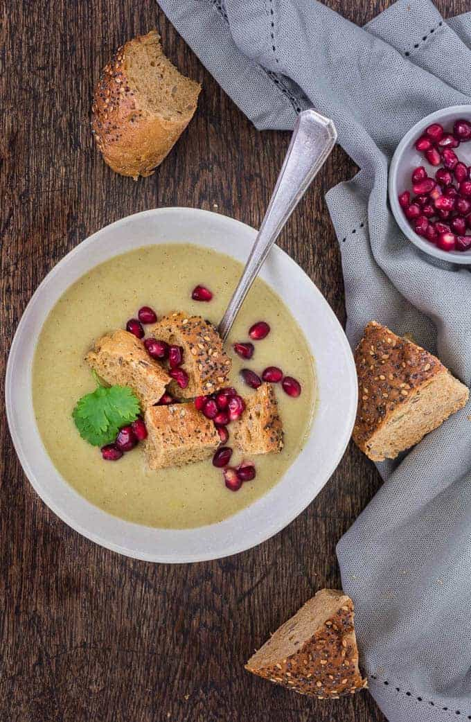 a bowl full of apple parsnip soup with herb and pomegranate garnish and s spoos