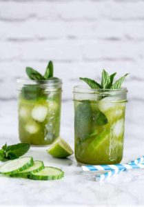 Cucumber Matcha Cocktail in 2 glasses garnished with mint and cucumber