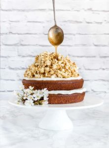 two layer plantain cake with coconut caramel popcorn and a spoon drizzling caramel on top
