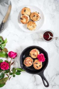 singin hinnes singing hinnies on a plate and cast iron pot with syrup and flowers on a table. | Recipes From A Pantry
