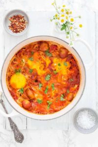 easy shakshuka recipe in a white pot on white background next to flours and pepper flakes