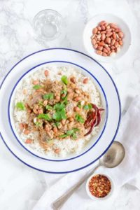 pork satay recipe with peanut sauce inside a white bowl on a white towel