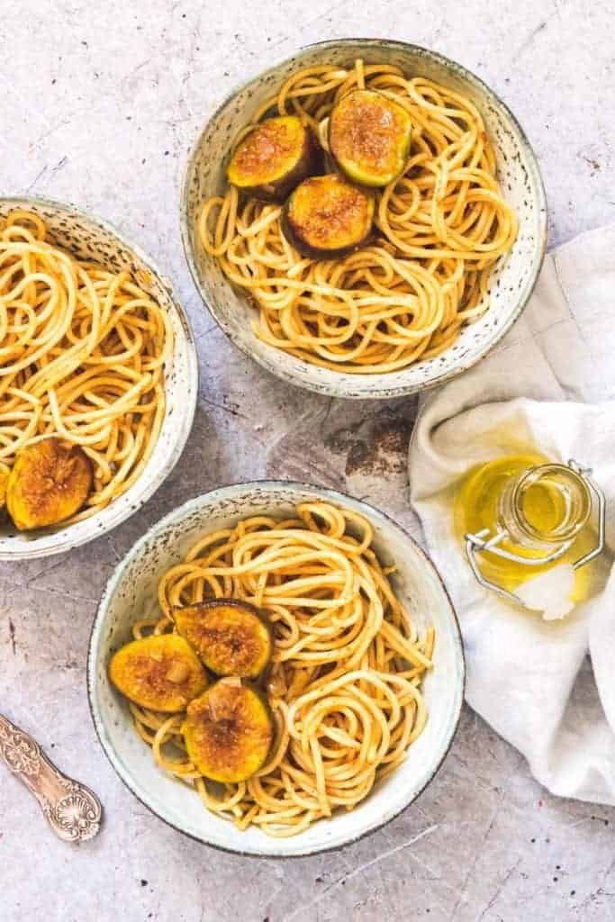 Three bowls of saffron sauce pasta with figs with some oil