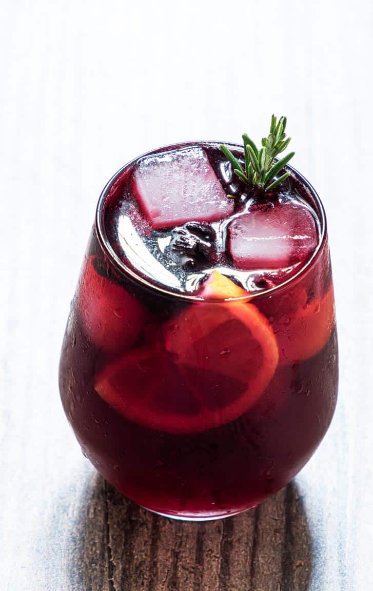 closeup view of a glass of hibiscus moscow mule garnished with lemon rosemary and ice