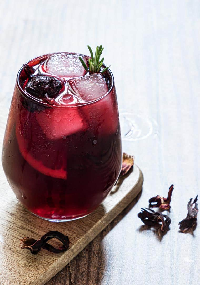 one glass filled with hibiscus moscow mule cocktail and set on a wood serving board