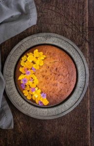 overhead view of cinnamon plantain cake with flowers on the left of the cake