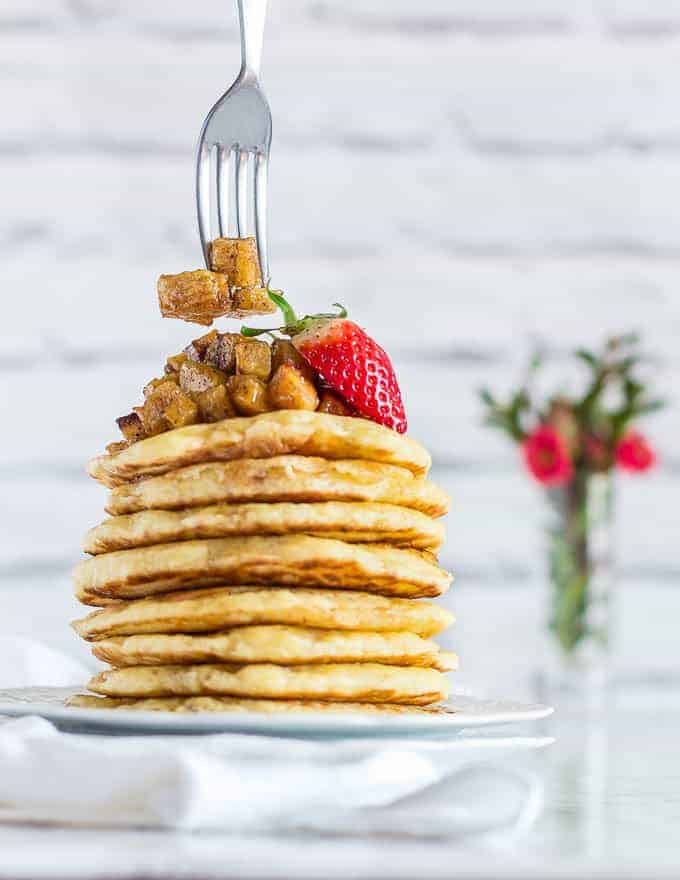 A stack of vegan pancakes (beghrir, baghrir) on a white plate toped with plantain cubes and strawberries. A fork is grabbing some plantains