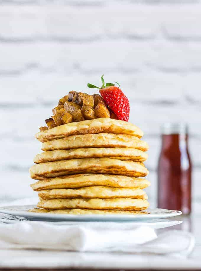 A stack of vegan pancakes (beghrir, baghrir) on a white plate toped with plantain cubes and strawberries