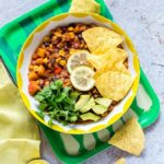 Slow cooker three bean chili in a bowl with toppings