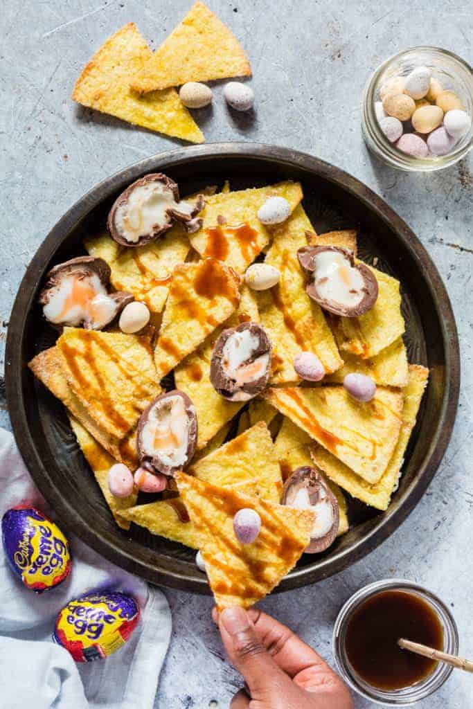 Cadbury crème egg nachos - Top down shot of homemade nachos in a bowl, caramel sauce, mini eggs and cadbury creme eggs with a hand taking some nachos