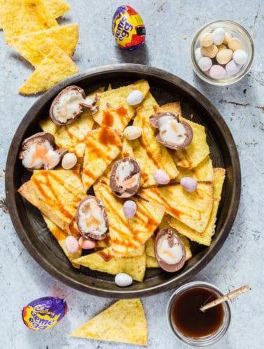 Cadbury crème egg nachos - Top down shot of homemade nachos in a bowl, caramel sauce, mini eggs and cadbury creme eggs