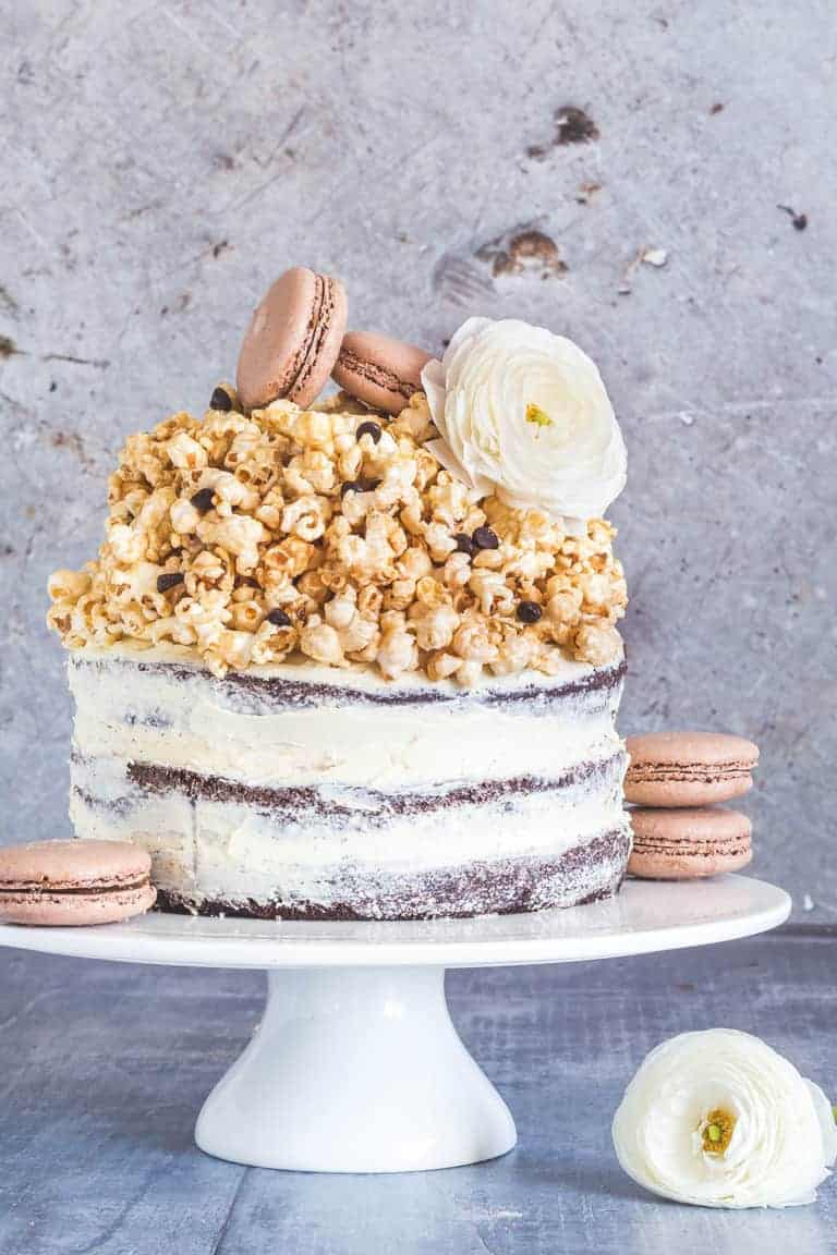 A three layer naked chocolate sponge cake with caramel popcorn decorated with macarons and flowers