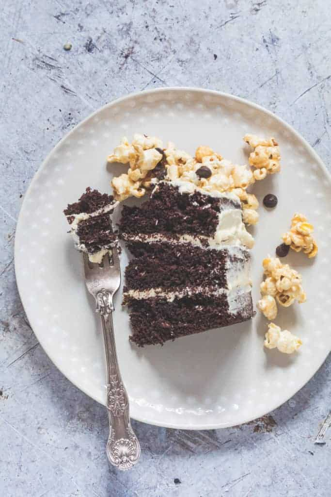 A slice of three layered moist chocolate cake with caramel popcorn on a plate with a forl