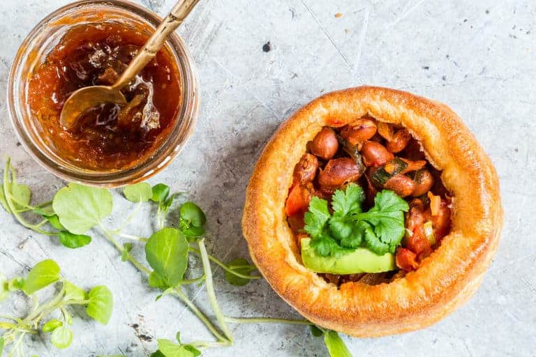 a bacon chilli pie garnished with avocado next to some chutney