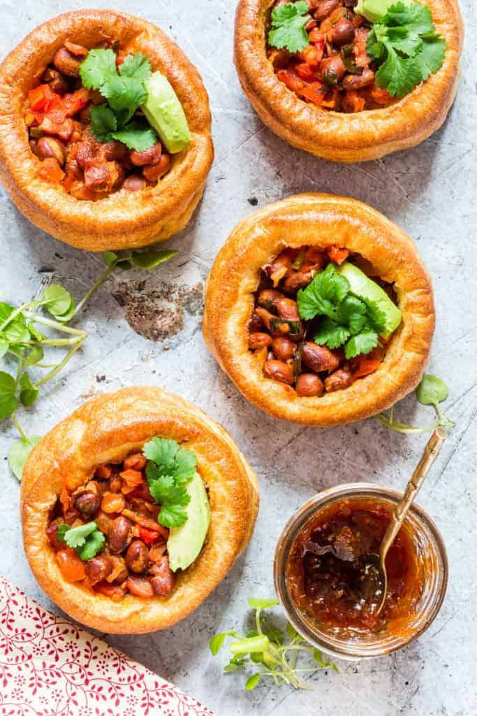 4 chilli bacon pies garnished with avocado and herbs with some chutney next to it.