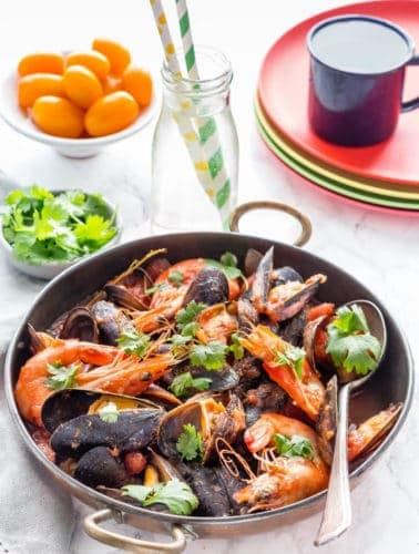 Over head shot of King Prawn and mussels Rougaille in a pot with coriander, tomatoes, flatbreads, chilli. Spoon and grey napkin too. Glass with green straw and yellow straw, 4 coloured plates and a blue cup