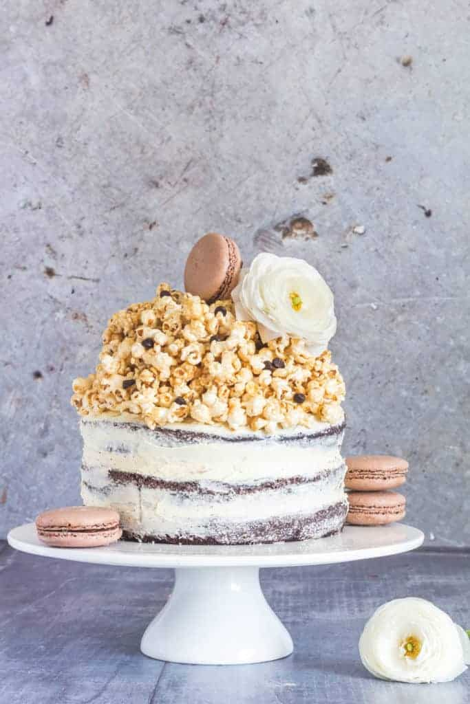 The best naked chocolate sponge cake topped with caramel popcorn, macrons and flowers