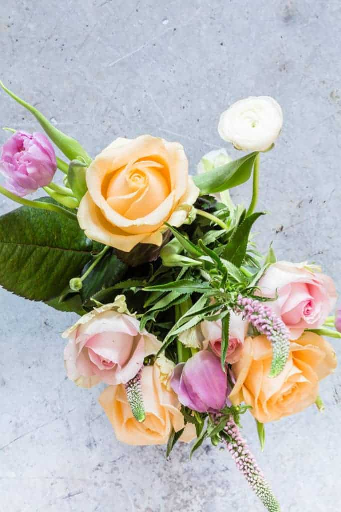 A bunch of orange, pink and white flowers on a grey table