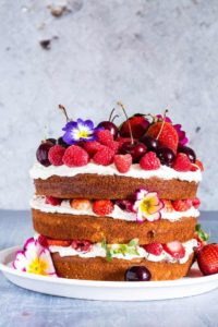 a layer cake - berry, orange blossom and elderflower cake with mascarpone cream topped with berries and flowers