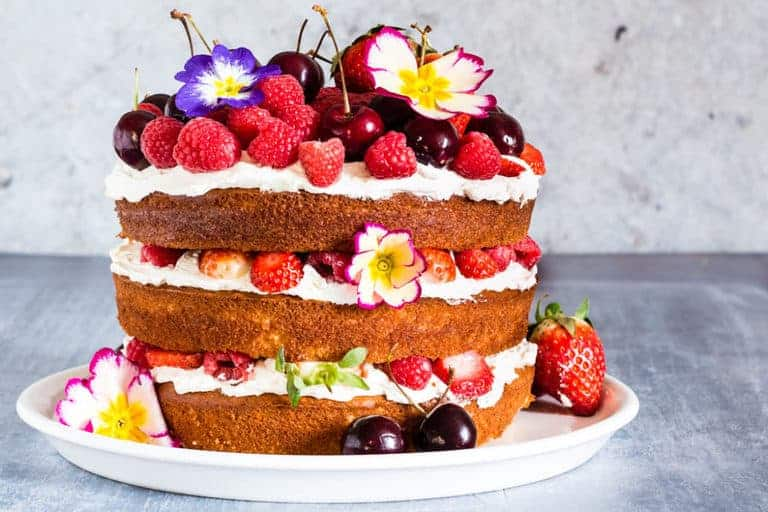 A three layer berry, orange blossom and elderflower cake with mascarpone whipped cream on a plate