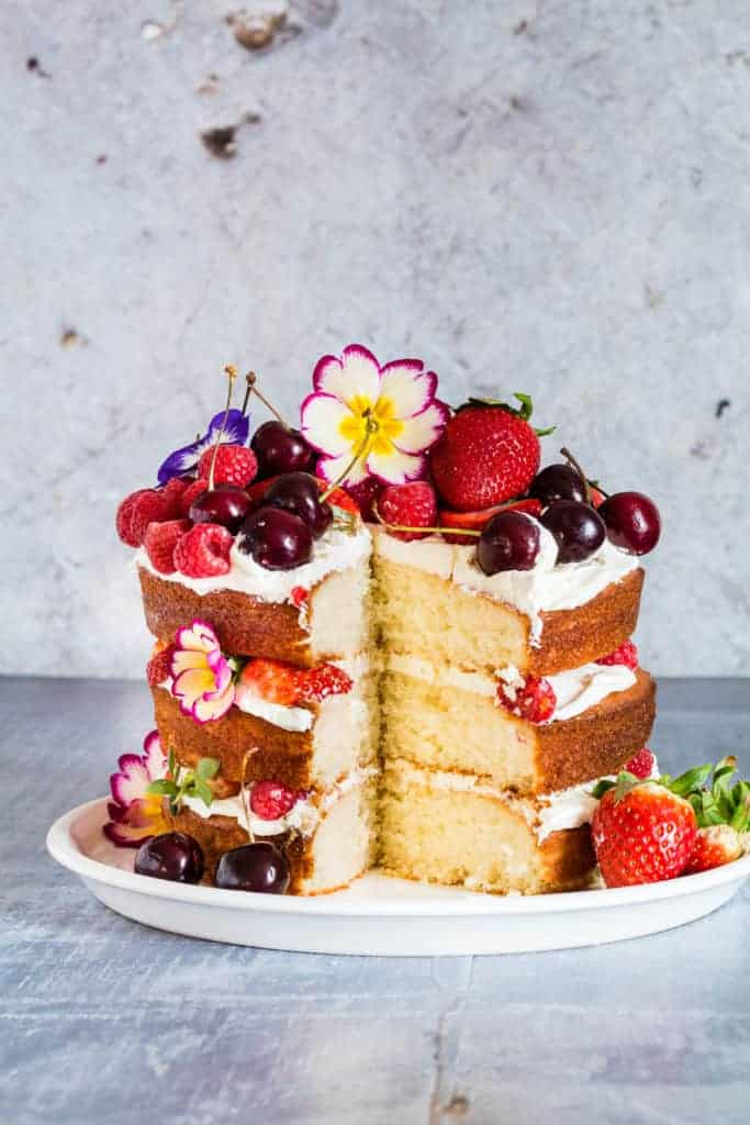 A three berry, orange blossom and elderflower cake with mascarpone whipped cream with a slice cut out