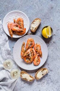 quick garlic butter chilli shrimps on a plate with lemon, buttered bread and wine