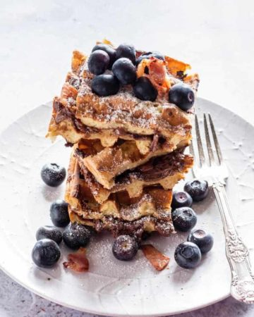 stack of decadent nutella waffles on a white plate with berries, bacon and a fork