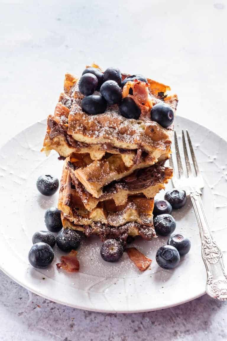These crispy bacon Nutella stuffed waffles make an amazing breakfast or brunch recipe. Add blueberries and maple syrup for an extra treat | Recipes From A Pantry