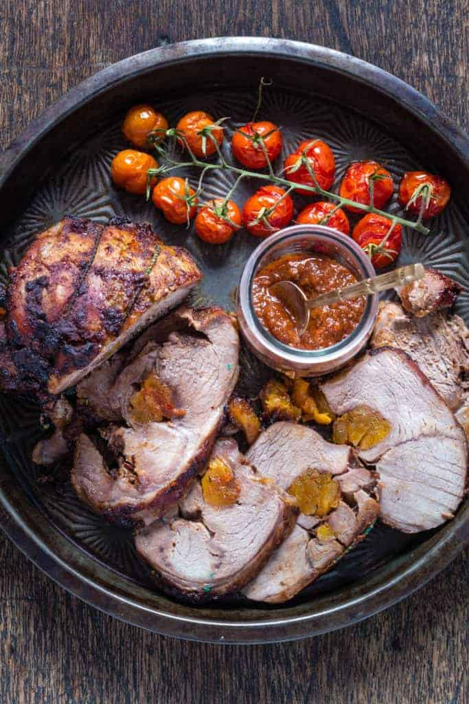 Sliced roast lamb shoulder stuffed with harissa apricots on a plate with tomatoes and harrisa