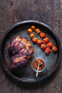 overhead shot of roast lamb shoulder with tomatoes and some harissa on a plate