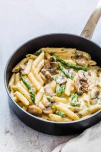 black skillet containing mushroom asparagus pasta in a sauce