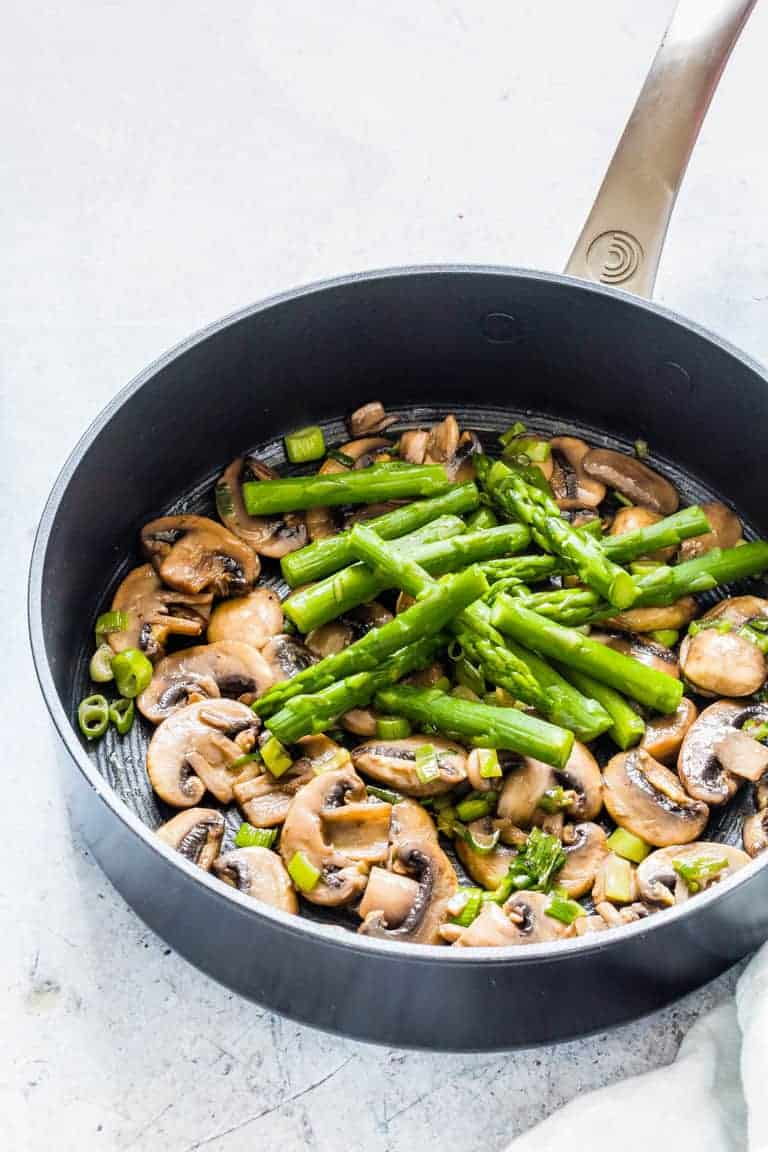 mushrooms and asparagus in a black pot with stainless steel handle being prepped for mushroom asparagus pasta
