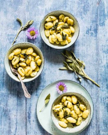 3 bowls of sage and brown butter gnocchi sauce over gnocchi on a table with extra sage