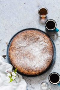 A courgette cake with coffee and syrup on a table