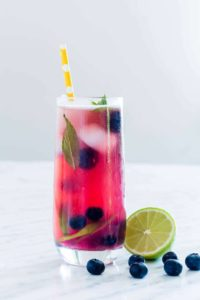 a glass of blueberry mojito with some lime and blueberries