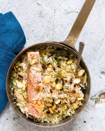 one pan salmon and rice with dill and almonds on a table