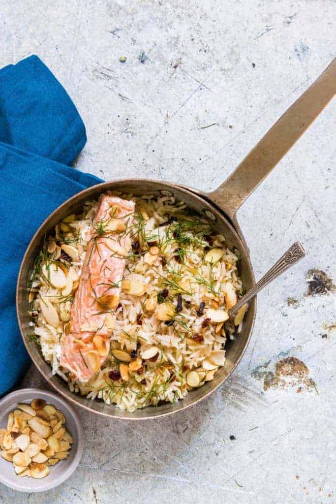 one pan salmon and rice on a table with some almonds flakes