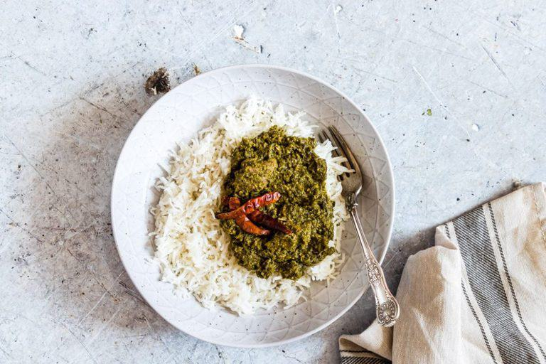 cassava leaf palava sauce - a bowl cassava leaf with rice and chilli, a fork in the bowl