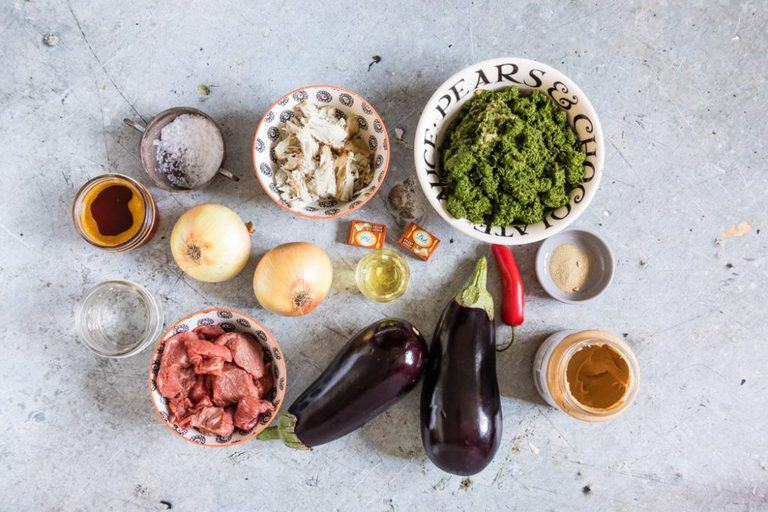 Ingredients to make cassava leaf sauce - aubergines, egg plant, onions, beef, palm oil, minced cassava leaves, peanut butter, chilli, ground coriander, stock cube, dried fish, salt and water