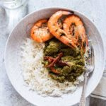 Overhead shot of a bowl of palava sauce - cooked cassava leaves with rice with prawns and chilli with a glass of water next to it