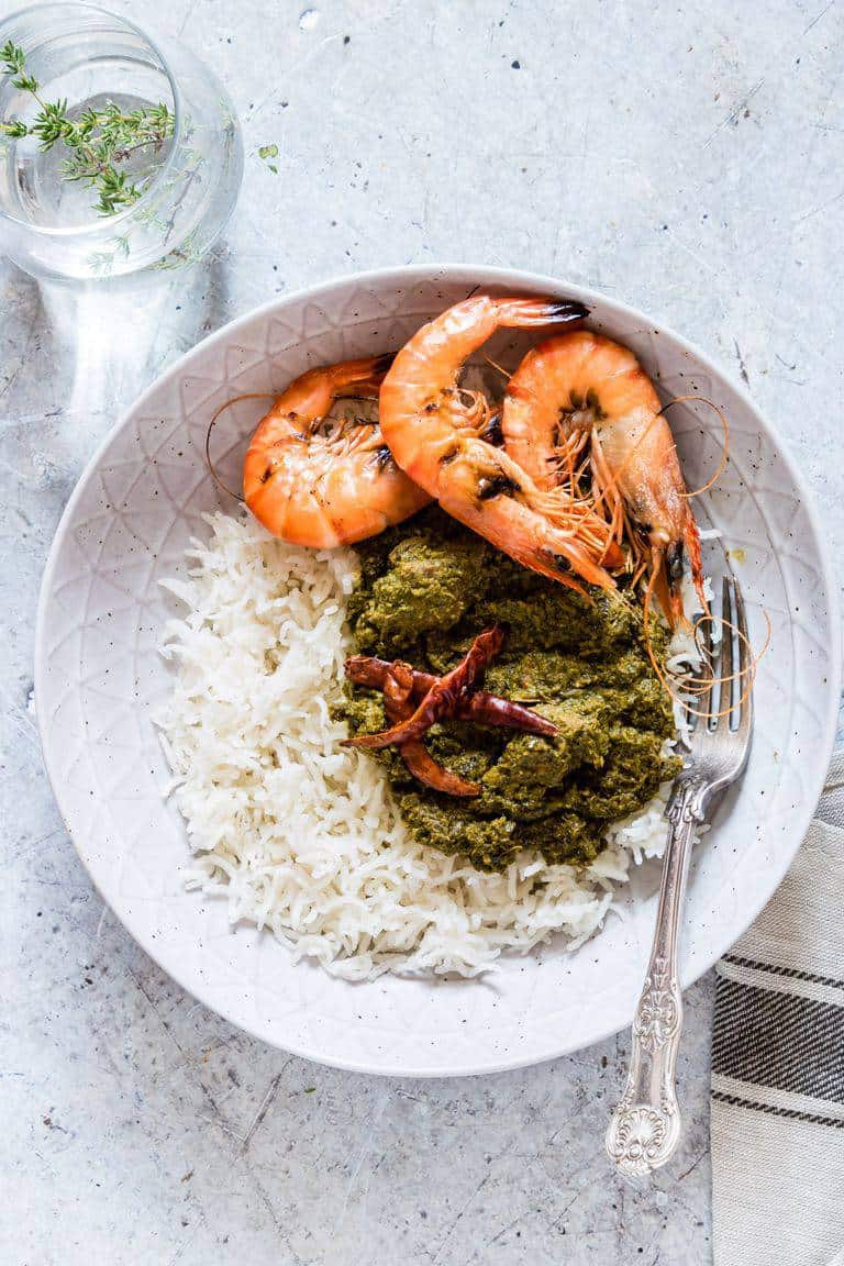 Overhead shot of a bowl of palava sauce - cassava leaves with rice with prawns and chilli with a glass of water next to it