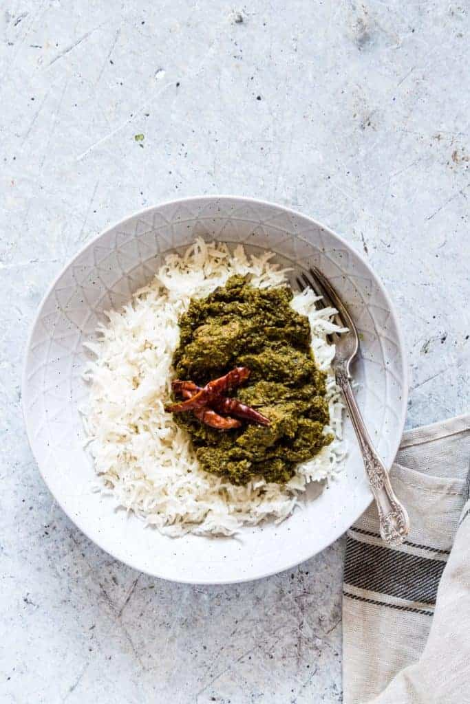Overhead shot of a bowl of palava sauce - cassava leaves with rice with chilli and a napkin next to it