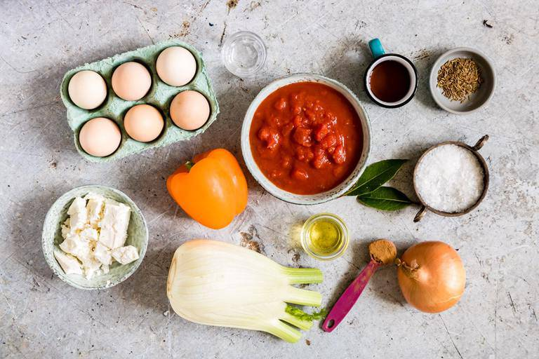 ingredients for shakshuka with feta on a countertop including eggs, tomatoes, fennel, an donions