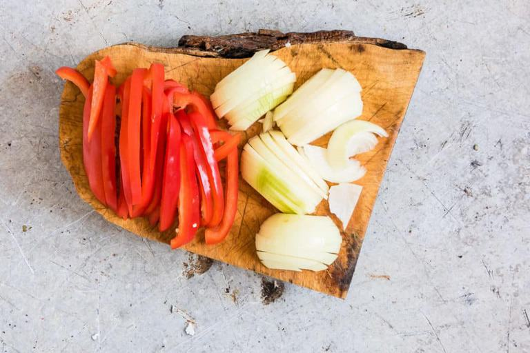 Peppers and onions on chopping board for chilli chicken recipe