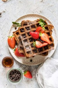 Delightfully fluffy & easy chocolate chip sweet potato waffles recipe with berries with a Halloween twist your guests will love. See more at recipesfromapantry.com #sweetpotatowaffles #easysweetpotatowaffles #chocolatechipwaffles #sweetpotatochocolatechipwaffles #wafflerecipes #halloweenrecipes