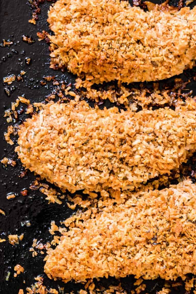 parmesan crusted chicken breasts on a hot pan being cooked
